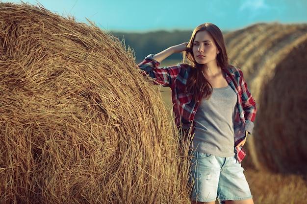 Portret van een jonge vrouw naast een stapel hooi