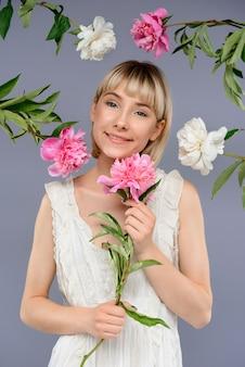 Portret van een jonge vrouw onder bloemen over grijze muur