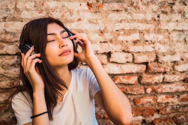 Portret van een jonge vrouw ontspant en luistert naar muziek met een koptelefoon tegen bakstenen muur