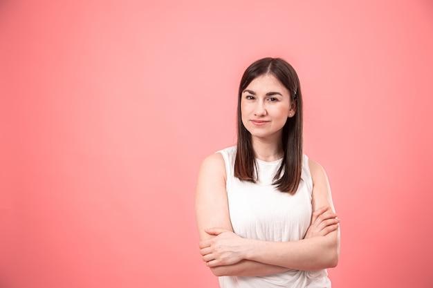 Portret van een jonge vrouw op een geïsoleerde roze achtergrond.