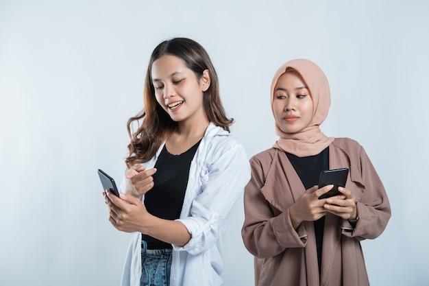 Portret van een jonge vrouw op een mobiel met universiteitsvriend