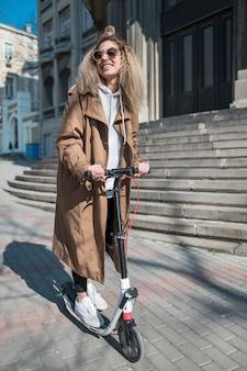 Portret van een jonge vrouw op elektrische scooter