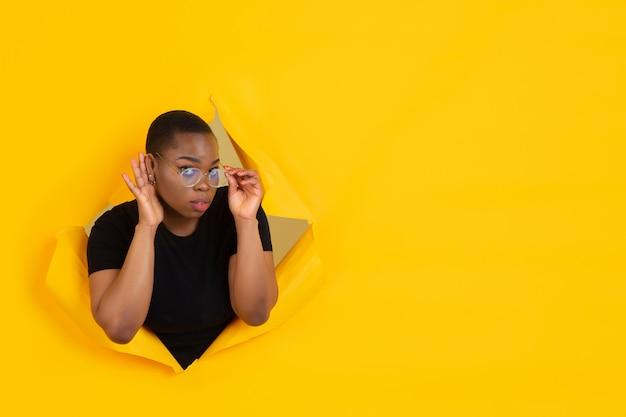 Portret van een jonge vrouw op gele gescheurde doorbraakachtergrond