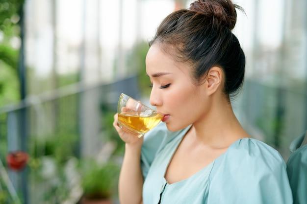 Portret van een jonge vrouw op het balkon met een kopje thee in de ochtend.