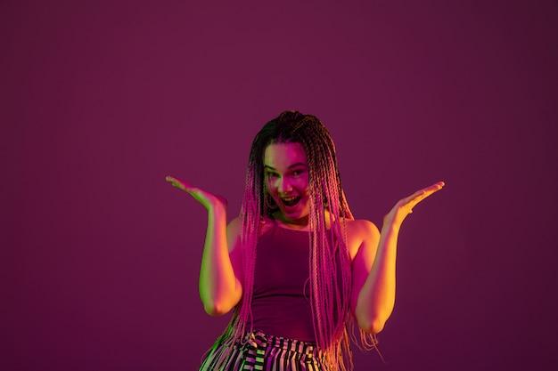 Portret van een jonge vrouw op roze muur met copyspace