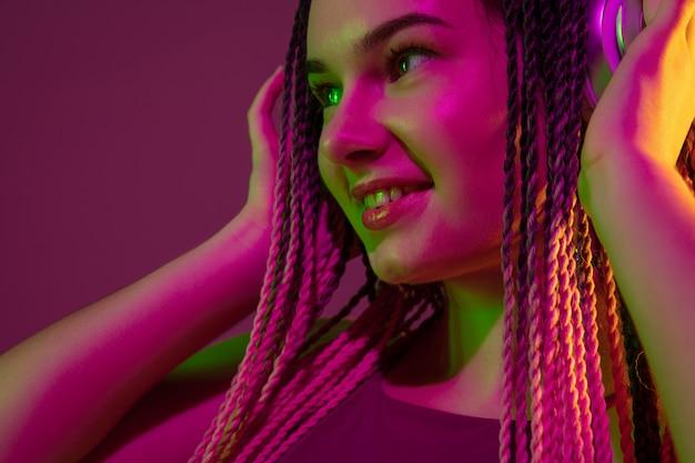 Portret van een jonge vrouw op roze muur met een koptelefoon