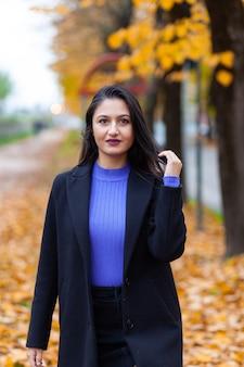 Portret van een jonge vrouw poseren in herfst park