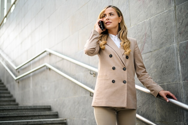 Portret van een jonge vrouw praten aan de telefoon op trappen buiten