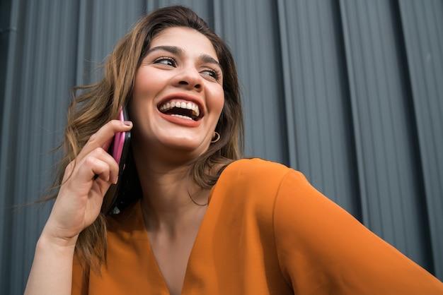 Portret van een jonge vrouw praten aan de telefoon terwijl ze buiten op straat staat