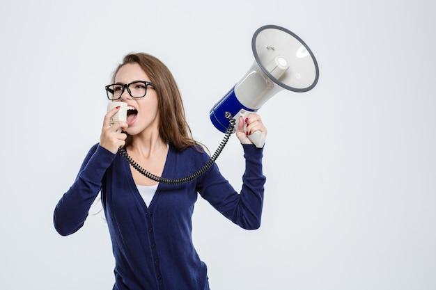 Portret van een jonge vrouw schreeuwend in megafoon geïsoleerd op een witte achtergrond white