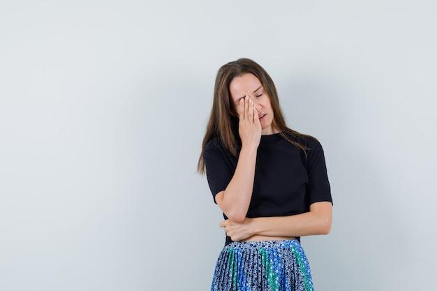 Portret van een jonge vrouw staande vingers gekruist in zwart t-shirt en blauwe rok en op zoek naar aantrekkelijk vooraanzicht
