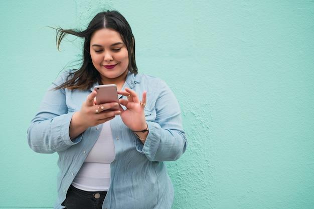Portret van een jonge vrouw tekstbericht typen op haar mobiele telefoon buitenshuis