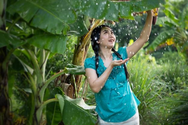 Portret van een jonge vrouw van azië met zwart haar die een banaanblad in het regenen houden bij de groene tuin