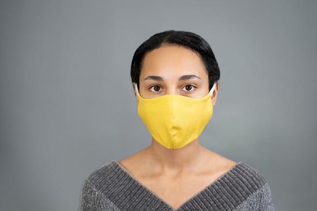 Portret van een jonge vrouw van gemengd ras met geel medisch masker close-up
