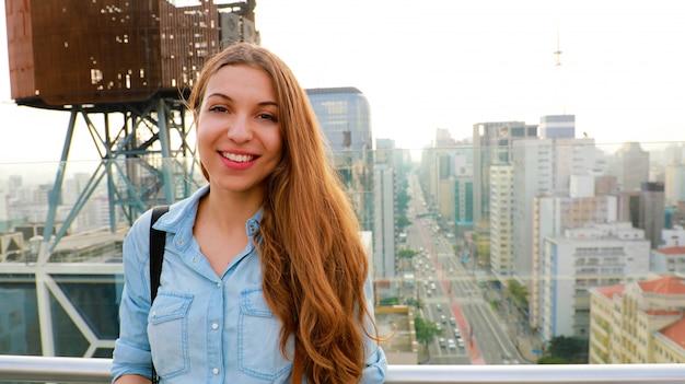 Portret van een jonge vrouw voor de skyline van sao paulo met paulista avenue, brazilië