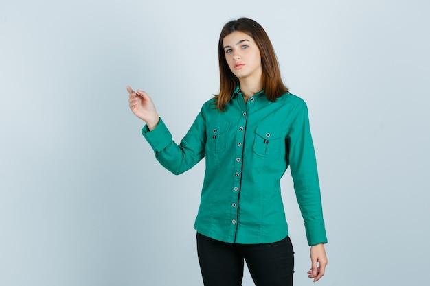 Portret van een jonge vrouw wijzend op de linkerbovenhoek in een groen shirt, broek en op zoek naar verward vooraanzicht