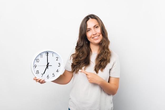 Portret van een jonge vrouw wijzend op een klok die ze vasthoudt.
