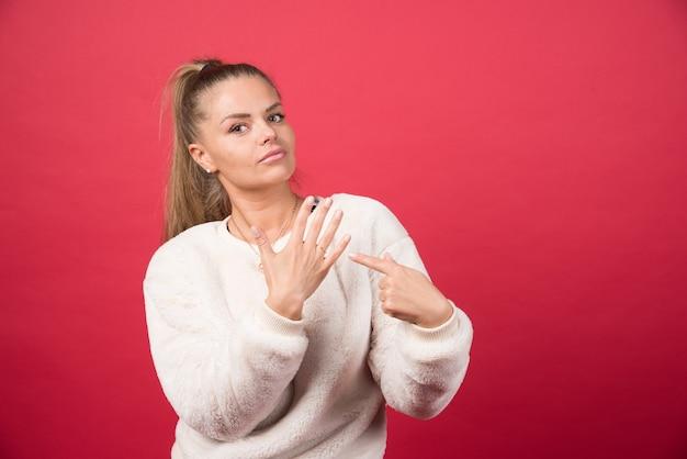 Portret van een jonge vrouw wijzend op haar hand hoge kwaliteit foto