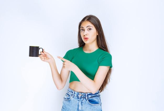 Portret van een jonge vrouw wijzend op kopje thee op witte achtergrond.