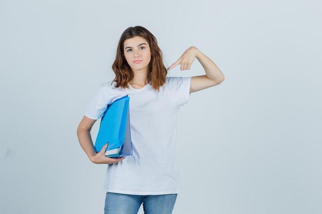 Portret van een jonge vrouw wijzend op mappen in wit t-shirt, spijkerbroek en op zoek naar zelfverzekerd vooraanzicht