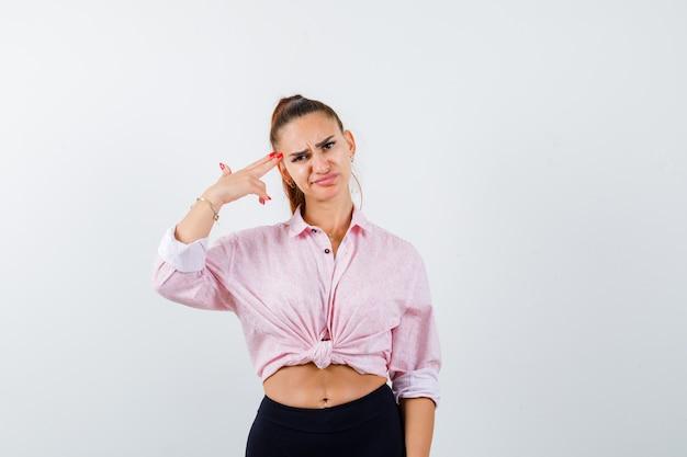 Portret van een jonge vrouw zelfmoordgebaar maken in casual shirt en hopeloos vooraanzicht op zoek