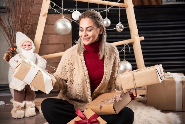 Portret van een jonge vrouw zitten en poseren met cadeautjes. foto van hoge kwaliteit