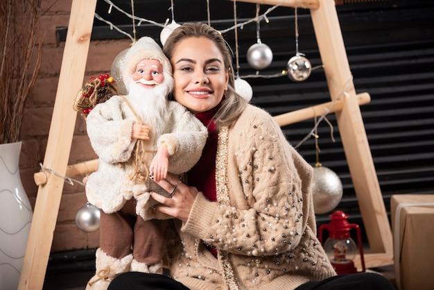 Portret van een jonge vrouw zitten en poseren met een speelgoed van de kerstman. foto van hoge kwaliteit