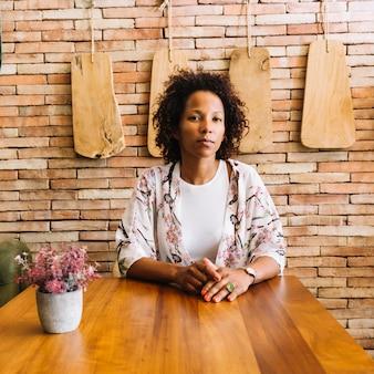 Portret van een jonge vrouw zitten in het restaurant