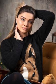 Portret van een jonge vrouw zittend op de bank en poseren. hoge kwaliteit foto