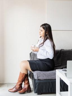 Portret van een jonge vrouw zittend op de bank koffie drinken wegkijken