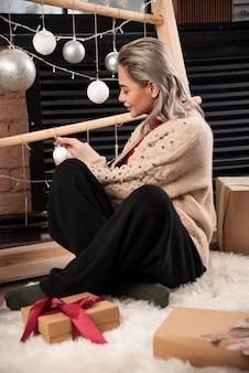 Portret van een jonge vrouw zittend op de vloer en met een kerstbal. foto van hoge kwaliteit