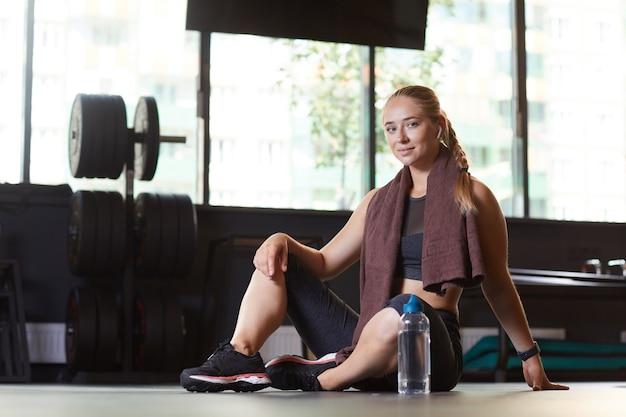 Portret van een jonge vrouw zittend op de vloer met een fles water en camera in de sportschool te kijken