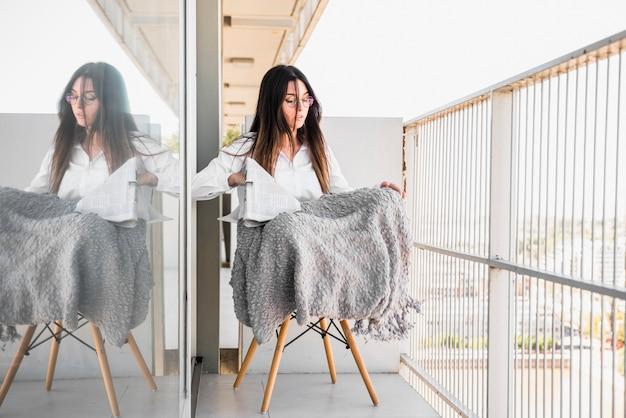 Portret van een jonge vrouw zittend op een stoel in het balkon bedrijf krant