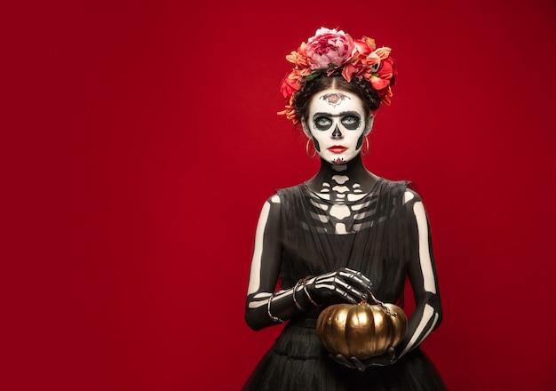 Portret van een jonge vrouw zoals santa muerte saint-dood of suikerschedel met lichte make-up. vrouw geïsoleerd op rode studio achtergrond met copyspace. het vieren van halloween of dag van de doden.