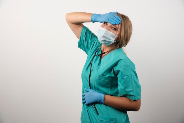 Portret van een jonge vrouwelijke arts die een beschermend masker draagt.