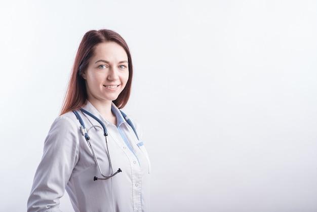 Portret van een jonge vrouwelijke arts in een wit uniform in de studio op een witte achtergrond met copyspace