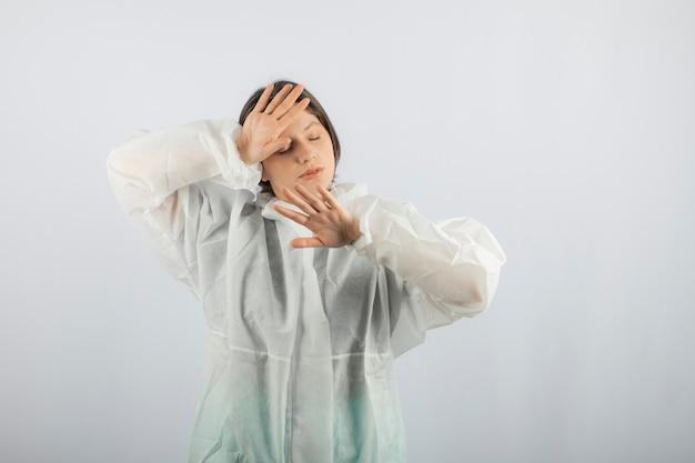 Portret van een jonge vrouwelijke arts-wetenschapper die een defensieve laboratoriumjas draagt.