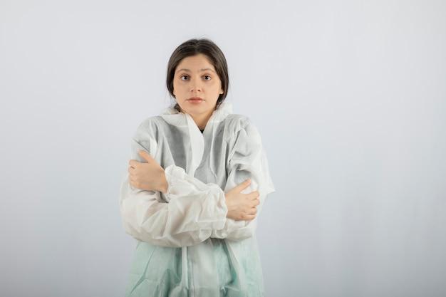 Portret van een jonge vrouwelijke arts-wetenschapper in defensieve laboratoriumjas die zichzelf knuffelt.