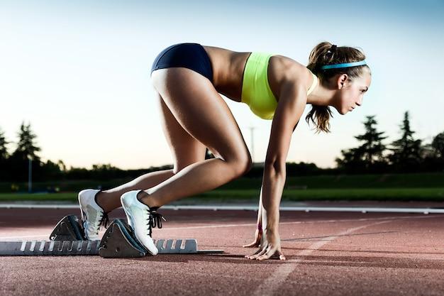 Portret van een jonge vrouwelijke atleet die van de startlijn lanceert in een race.