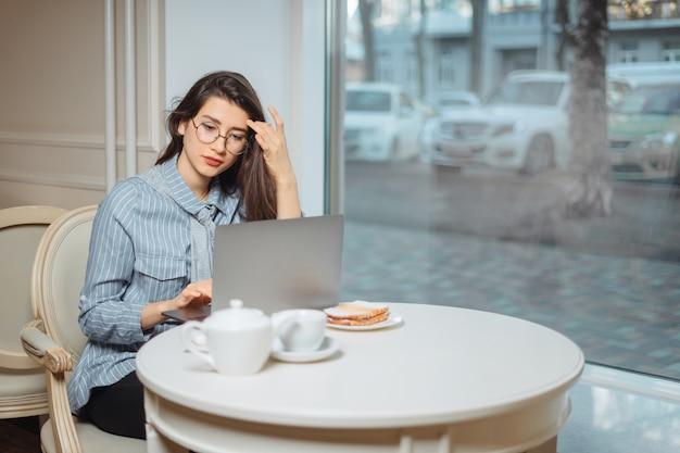 Portret van een jonge vrouwelijke freelancer die laptop computer voor afstandsbaan met behulp van zittend in moderne coffeeshop interieur, slimme vrouw bezig met net-boek tijdens ochtendontbijt in café-bar