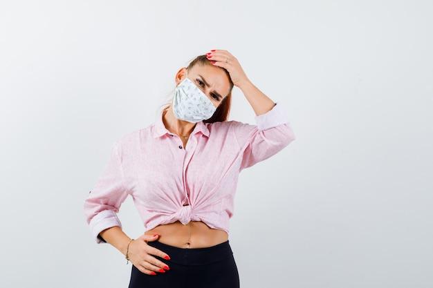 Portret van een jonge vrouwelijke hand op het hoofd in shirt, broek, medisch masker en op zoek naar vergeetachtig vooraanzicht