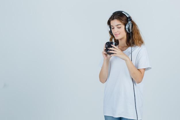 Portret van een jonge vrouwelijke kopje drank in wit t-shirt te houden en op zoek verrukt vooraanzicht
