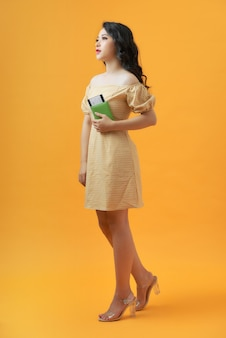 Portret van een jonge vrouwelijke reiziger met een internationaal in hand paspoort over geel