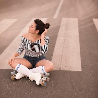 Portret van een jonge vrouwelijke skater zittend op de weg