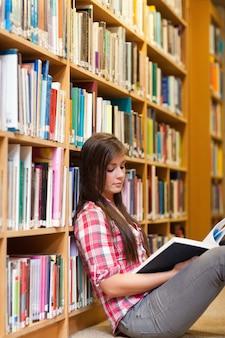 Portret van een jonge vrouwelijke student die een boek leest