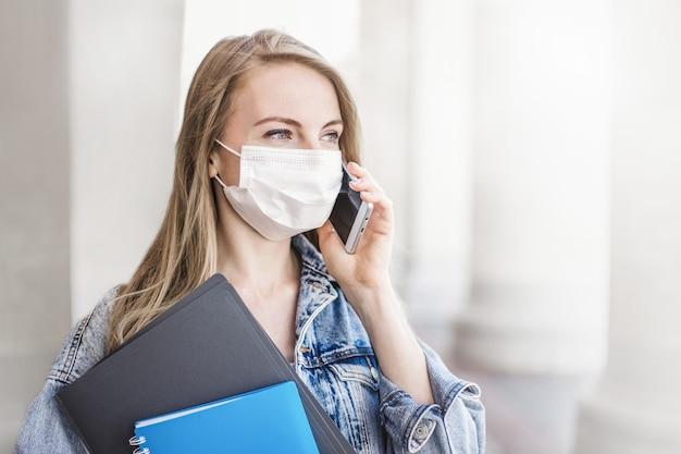 Portret van een jonge vrouwelijke student die een medisch masker draagt en op straat staat aan de universiteit met een mobiele telefoon tijdens quarantaine covid 19, kopie ruimte