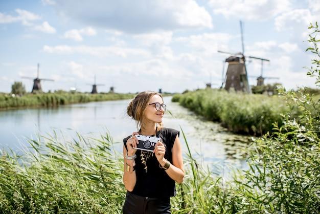 Portret van een jonge vrouwelijke toerist die met een fotocamera op de prachtige landschapsachtergrond staat met oude windmolens in nederland