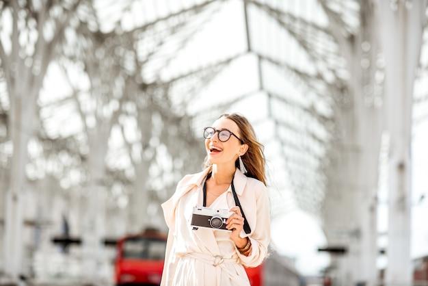 Portret van een jonge vrouwelijke toerist die met fotocamera buiten loopt op het treinstation