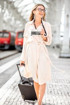 Portret van een jonge vrouwelijke toerist die met koffer en fotocamera buiten loopt op het treinstation