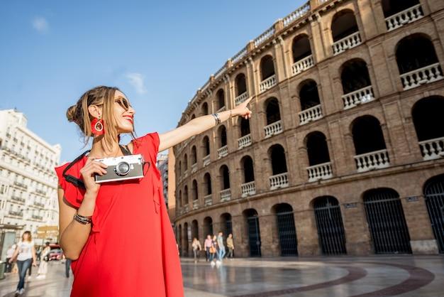 Portret van een jonge vrouwelijke toerist in een rode jurk die met een fotocamera staat voor het amfitheater van de arena in de stad valencia, spanje